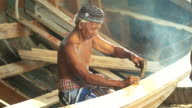 Asian elderly carpenter making wooden boat.