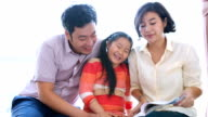Asian family reading book