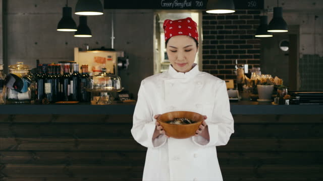 Asian Female Chef Showing Her Cooked Meal Proudly
