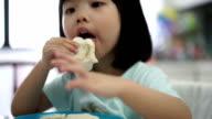 Asian female child enjoying her breakfast