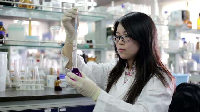Asian female scientist looking at beaker of liquid