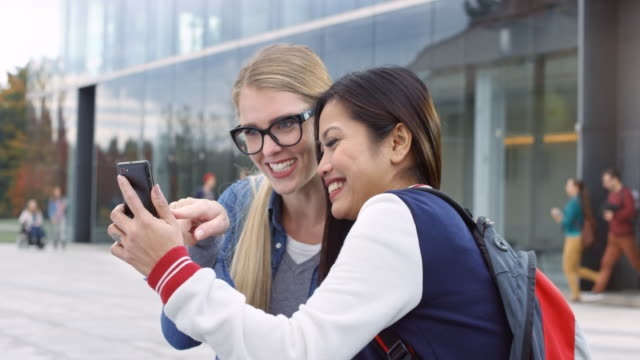 Asian female student and her Caucasian female friend smiling and talking while scrolling on the smartphone