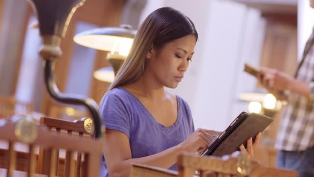 LD Aziatische vrouwelijke student met behulp van een tablet in de bibliotheek