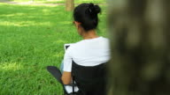Asian female using digital device for stock market trading at the park in Chiang Mai Province Thailand