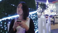 Asian female using smartphone urban night scene contrast with rush city light and christmas tree background