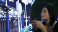 Asian female using smartphone urban night scene slow motion with rush city light and christmas tree background