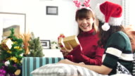 Asian Friendship Giving Christmas gifts in living room