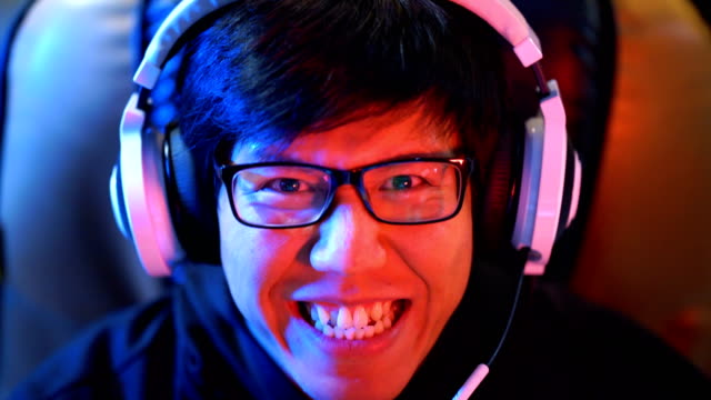 Asian Gamer looking to the camera with reflection of gaming in his glasses