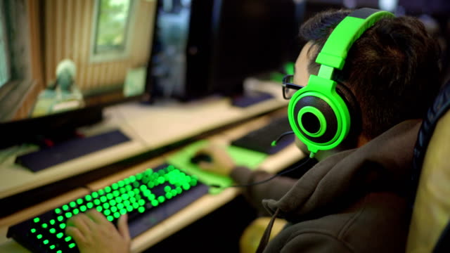 Asian gamer playing First-person shooter in internet cafe