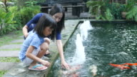 Asian girl and mother feeding food for carp fish in pond