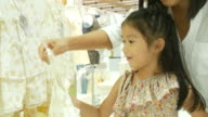 Asian girl and mother having fun shopping together