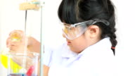 asian girl doing an experiment in laboratory with lab tubes