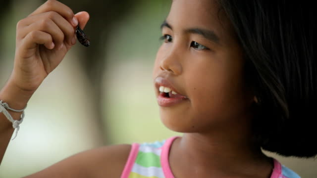 Asian girl eating insects