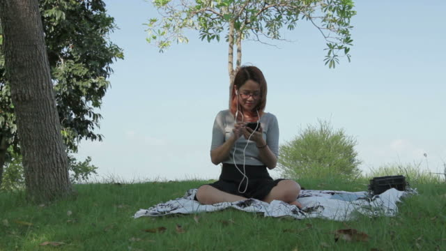 Asian girl picnic in the park enjoy listening music from smartphone