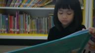 Aziatisch meisje leesboek in bibliotheek