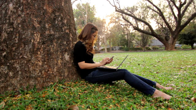 Asian girl relax with smartphone and laptop on her knee