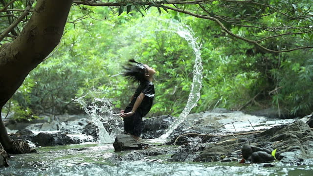 HD: Asian girl splashing water with her hair in the waterfall.