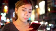 Asiatin mit Handy während zu Fuß, auf Straßen der Nacht Stadt