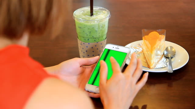 Asian girl using smartphone Green screen Digital tablet with cake and green tea.