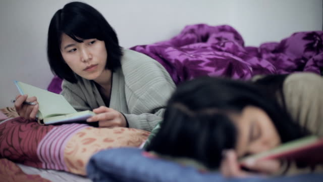 Asian girl waking up her exhausted sleeping friend for studies.