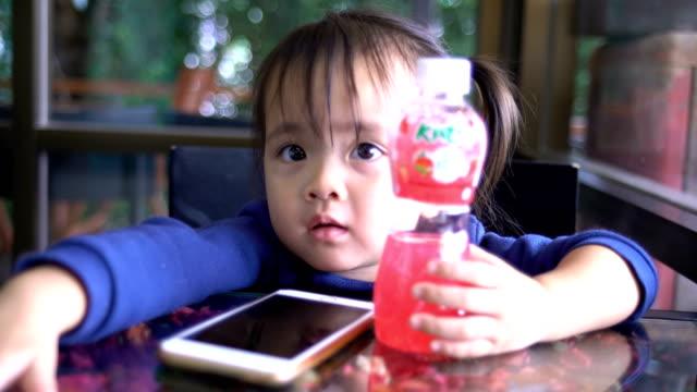 Asiatiska flickor Använd telefonen i en restaurang.