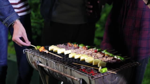 Asiatische Gruppe von Freunden, Grill und gegrillte Fischspieße auf Rost Partei im Garten