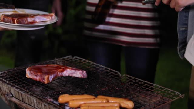 Asiatische Gruppe von Freunden, Grill und gegrillte Fischspieße auf Rost Party mit Bier im Garten