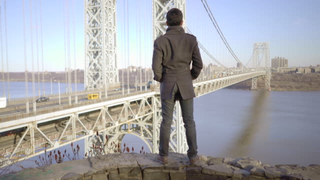 Asian Guy Standing on Shore and Looking at View. Bridge and Skyscrapers in the Background.
