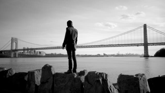 Asian Guy Standing on Shore and Looking at View. Bridge and Skyscrapers in the Background. Black and White.