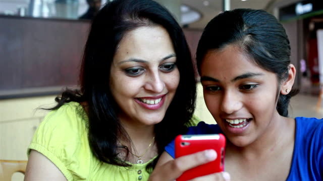 Asian Indian Mother and Daughter using Phone reading SMS