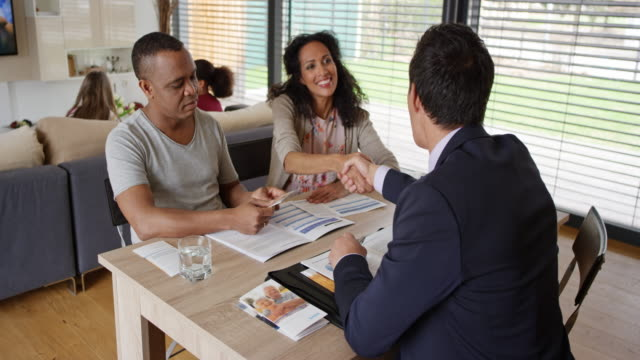 Asian insurance agent shaking hands with a couple on a meeting in their home