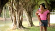 Asian kids piggyback at the park