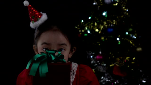 Asian little girl opening christmas gift box