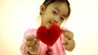 Asian little girl showing red heart pillow