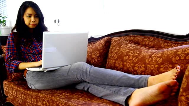 Asiatische auf dem sofa liegende labtop verwenden
