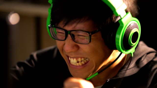 Asian male gamer celebrating his winning in computer game battle