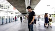 Asian male using smart phone urban scene