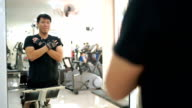 Asian man building back muscle in gym