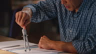Asian man drawing with compasses behind his desk