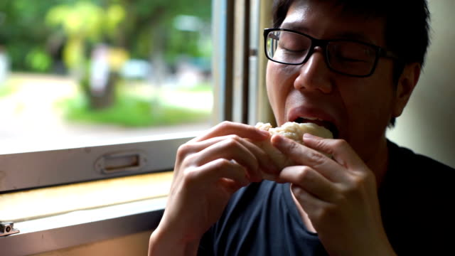 Asian Man eating Chinese Bun while Traveling in Local Train