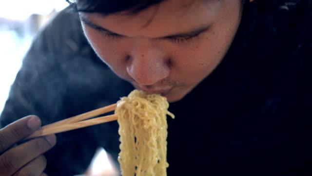 Asian man eating ramen