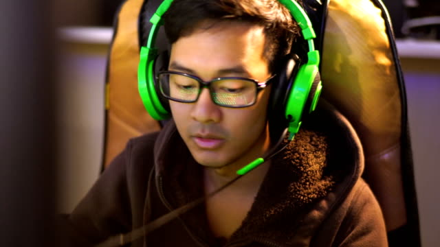 Asian Man Gaming in Cafe with Green Gaming headset