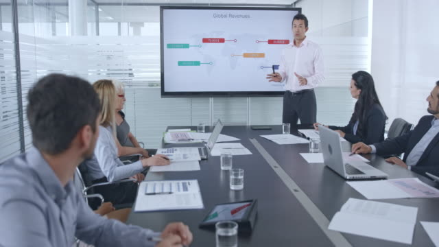 Asian man giving a financial presentation to his colleagues in the conference room