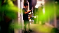 A asian man in headphones listening to music on mobile phone while standing on street at night.