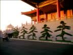 Asian man rides rickshaw bicycle past row of ornamental trees outside temple, China.