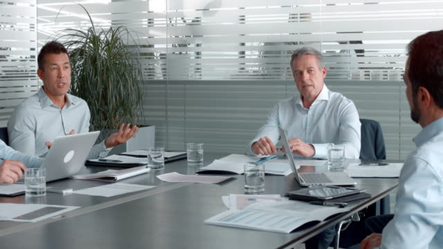 Asian man talking in a meeting with the project manager and colleagues in the conference room
