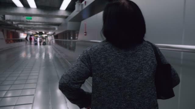 Reife Asiatin Wandern in Flughafen