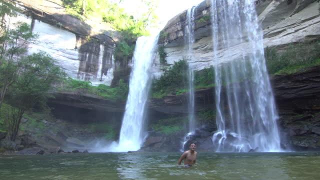 Asiatiska män spelar vattenfall