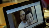 4K: Asian mom and son on video call facetime chatting via laptop computer