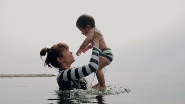Aziatische moeder en kind plezier In zwembad